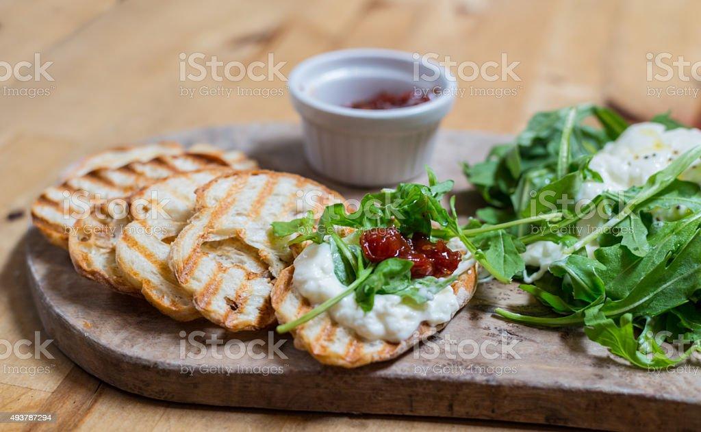 Burrata on toast with arugula and jam stock photo