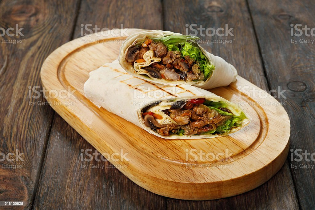 Burrito with pork meat and vegetables at wood desk stock photo