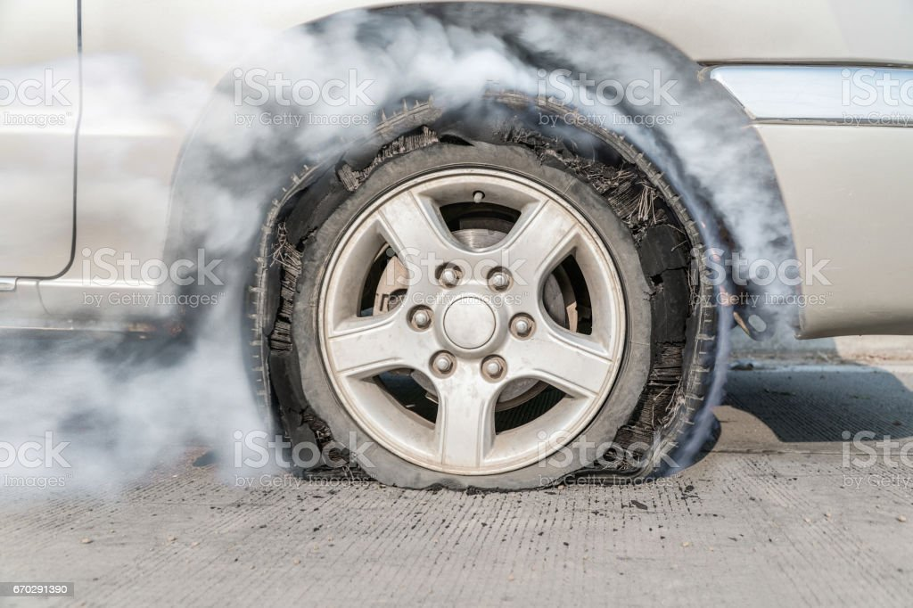 burst tire on the road stock photo