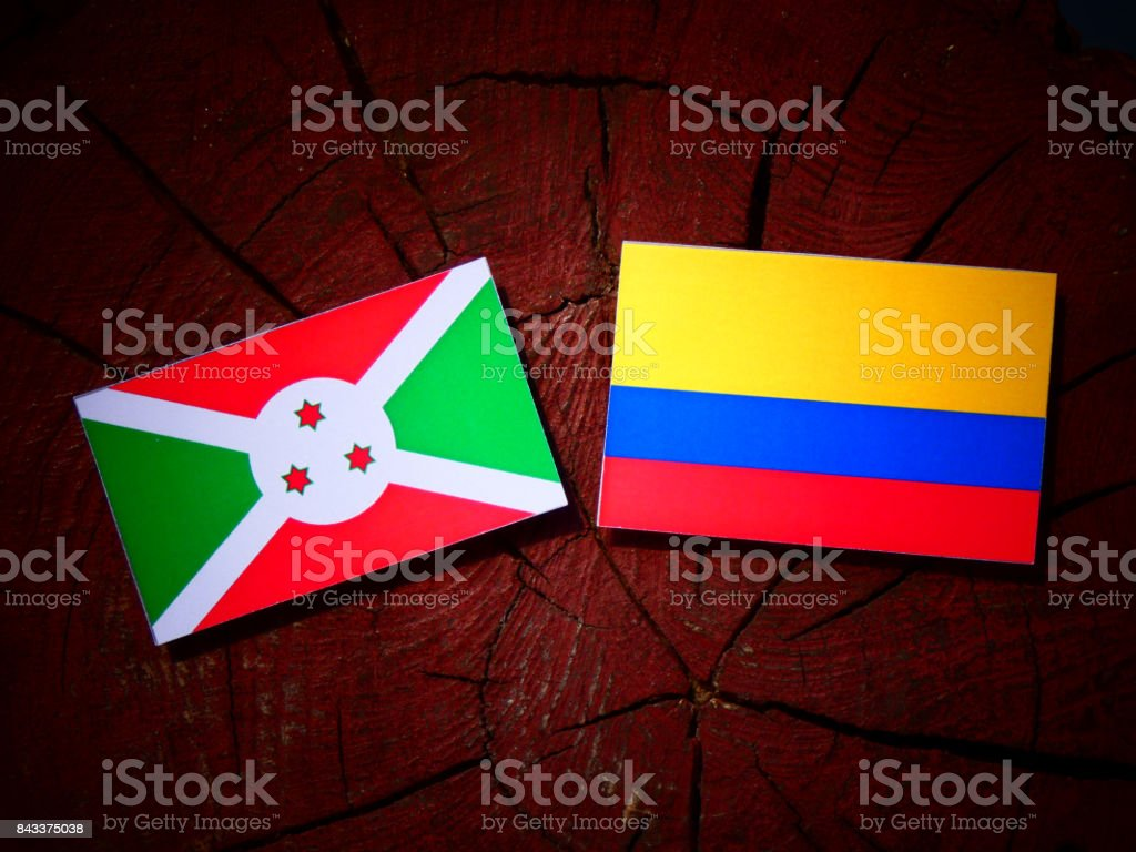 Burundi flag with Colombian flag on a tree stump isolated stock photo