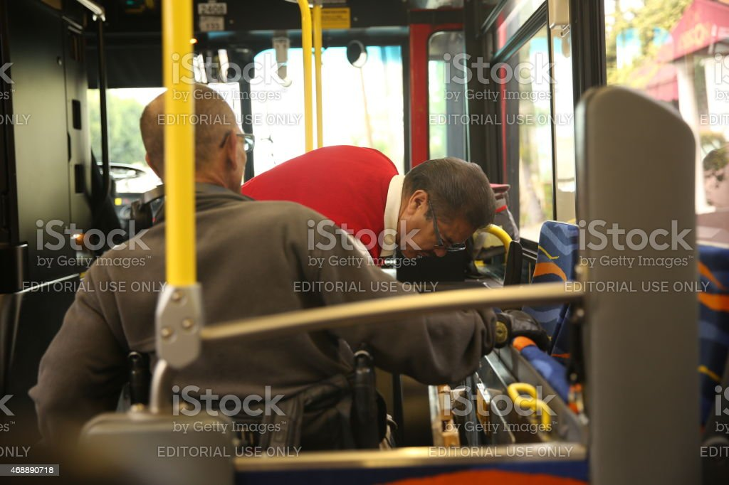 Bus driver help the disabled gentleman to leave the bus stock photo