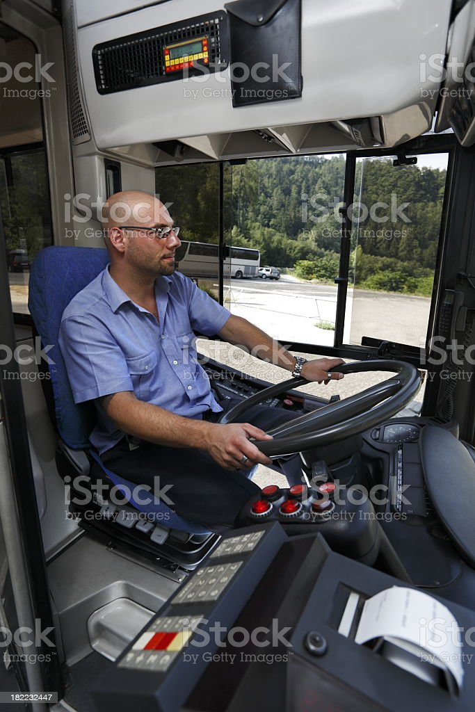 A bus driver in a blue shirt looking at the road stock photo