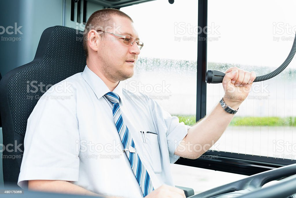 Bus driver making announcement using microphone stock photo