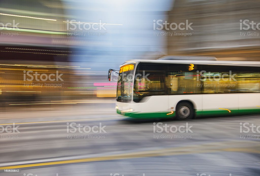 Bus driving on city street stock photo