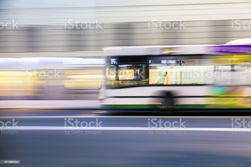Bus driving on city street stock photo