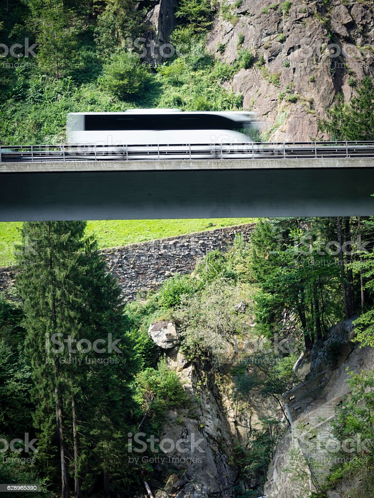 Bus driving on suspended highway / alpine mountain viaduct stock photo