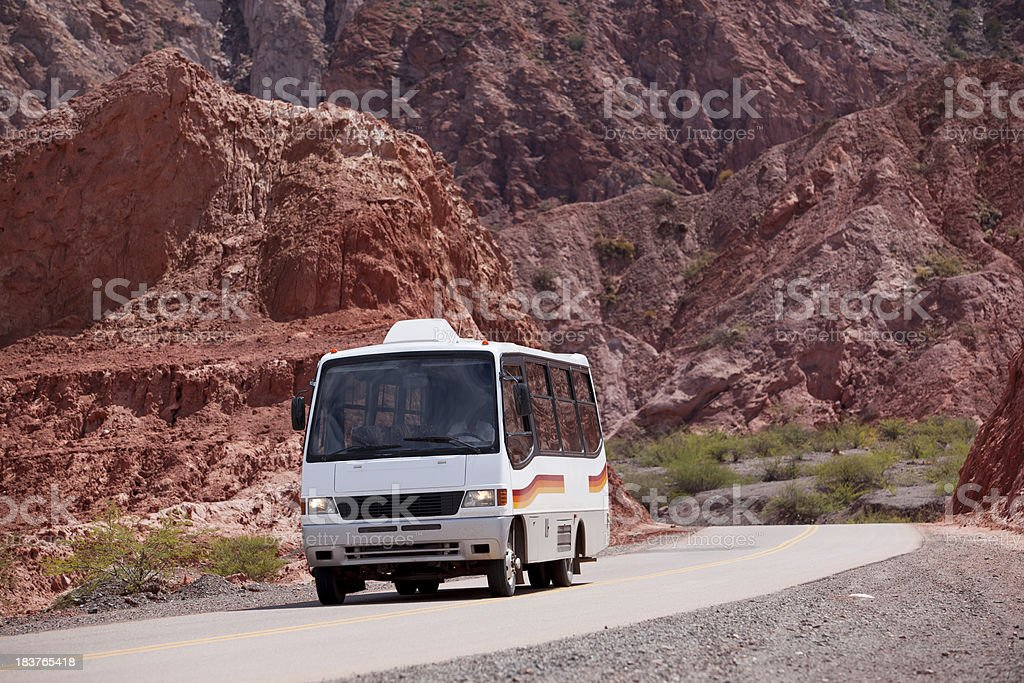 Bus driving through valley in the north of Argentina stock photo