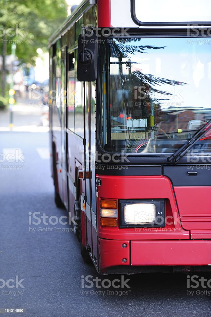 Bus in the city traffic, green trees background stock photo