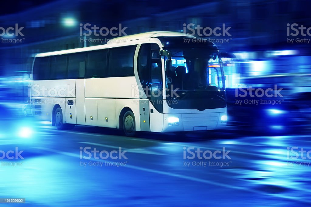 bus moves in the night city stock photo