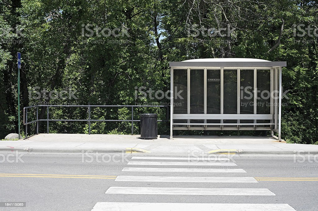 Bus shelter with crosswalk and forest royalty-free stock photo