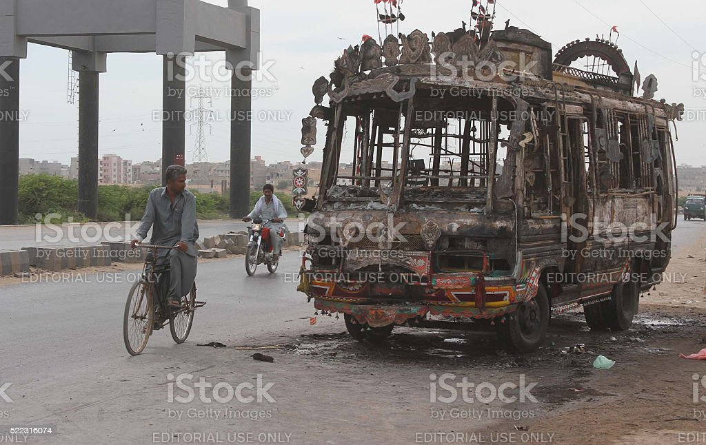 Bus torched by angry mob after road accident stock photo