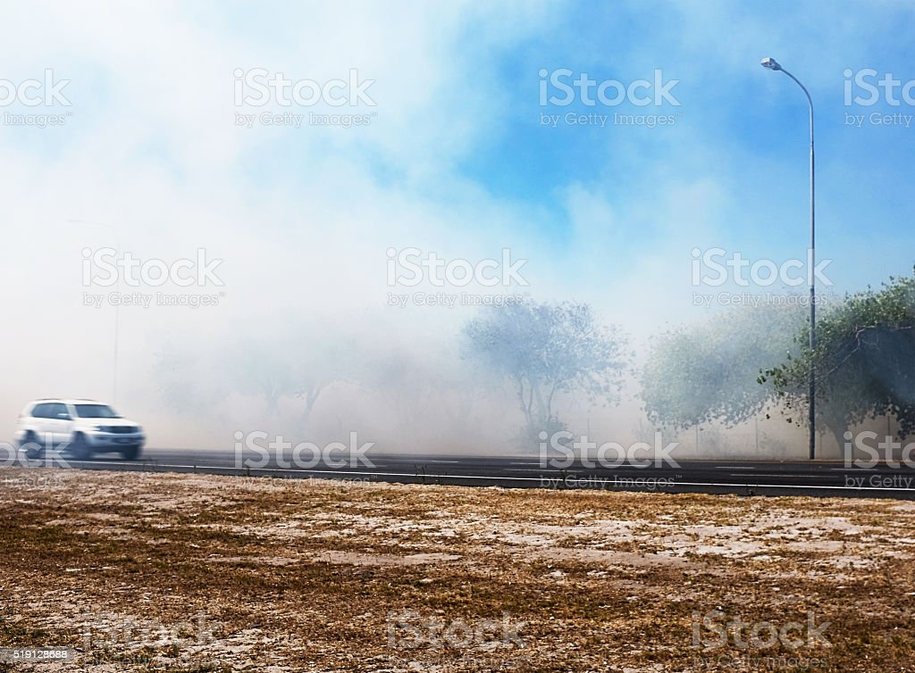 Bushfire by road during summer drought, car passing by stock photo