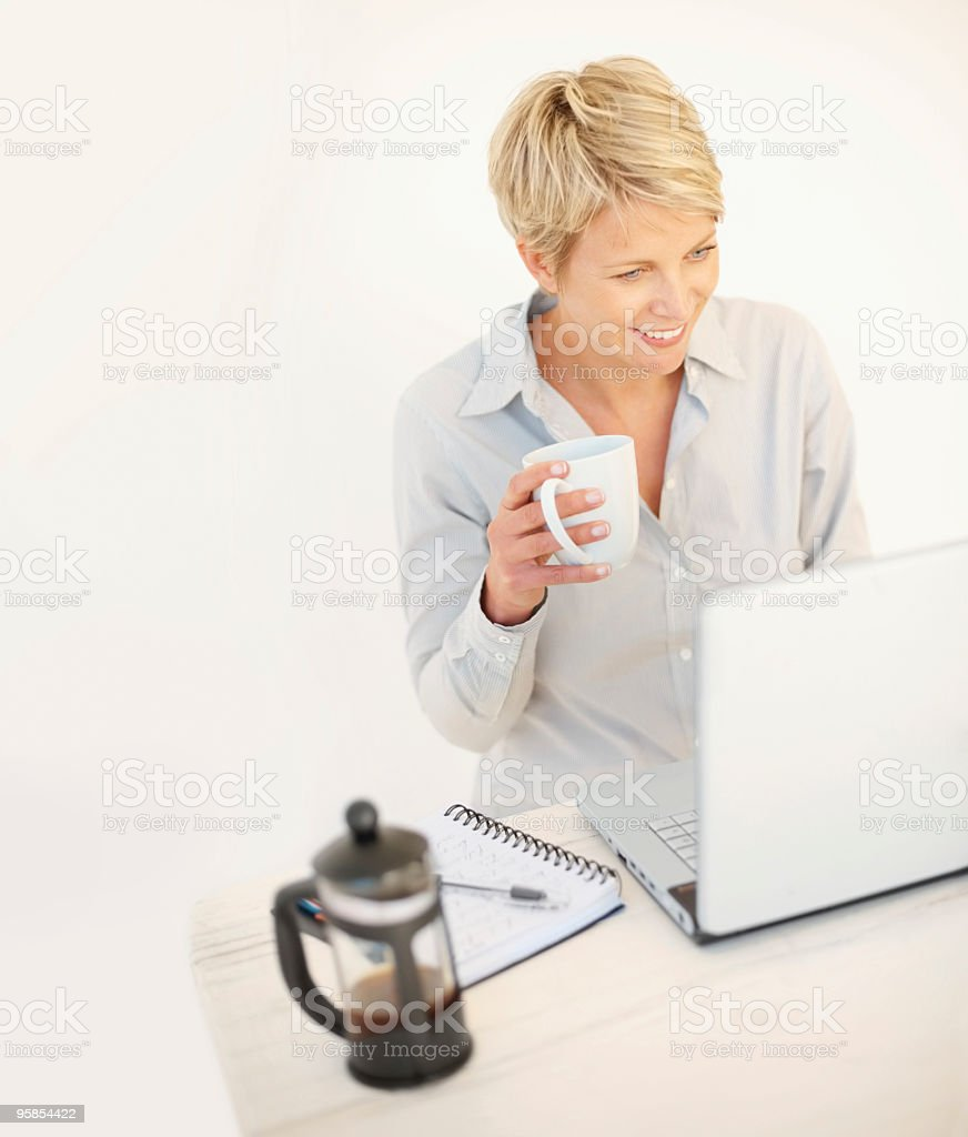 Busines woman having coffee while working on a laptop royalty-free stock photo