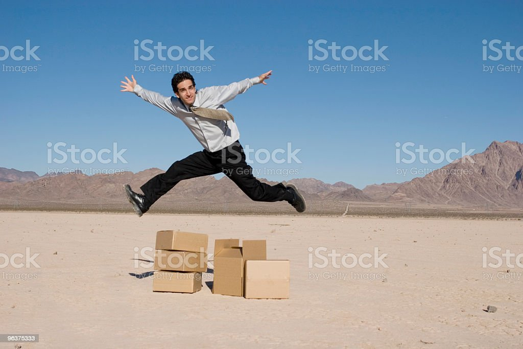 Businesman jumping over boxes royalty-free stock photo