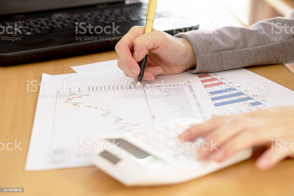 Business adviser are working to analyze company data from chart stock photo
