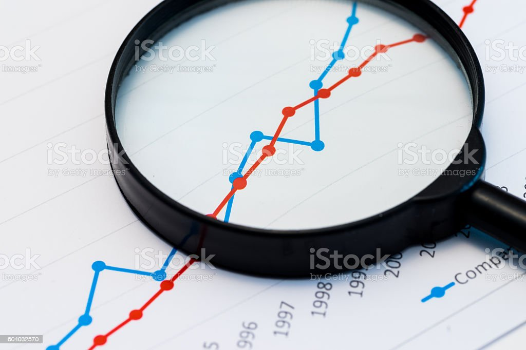 Business Analysis Image - magnifying glass on graphs and spreadsheet stock photo