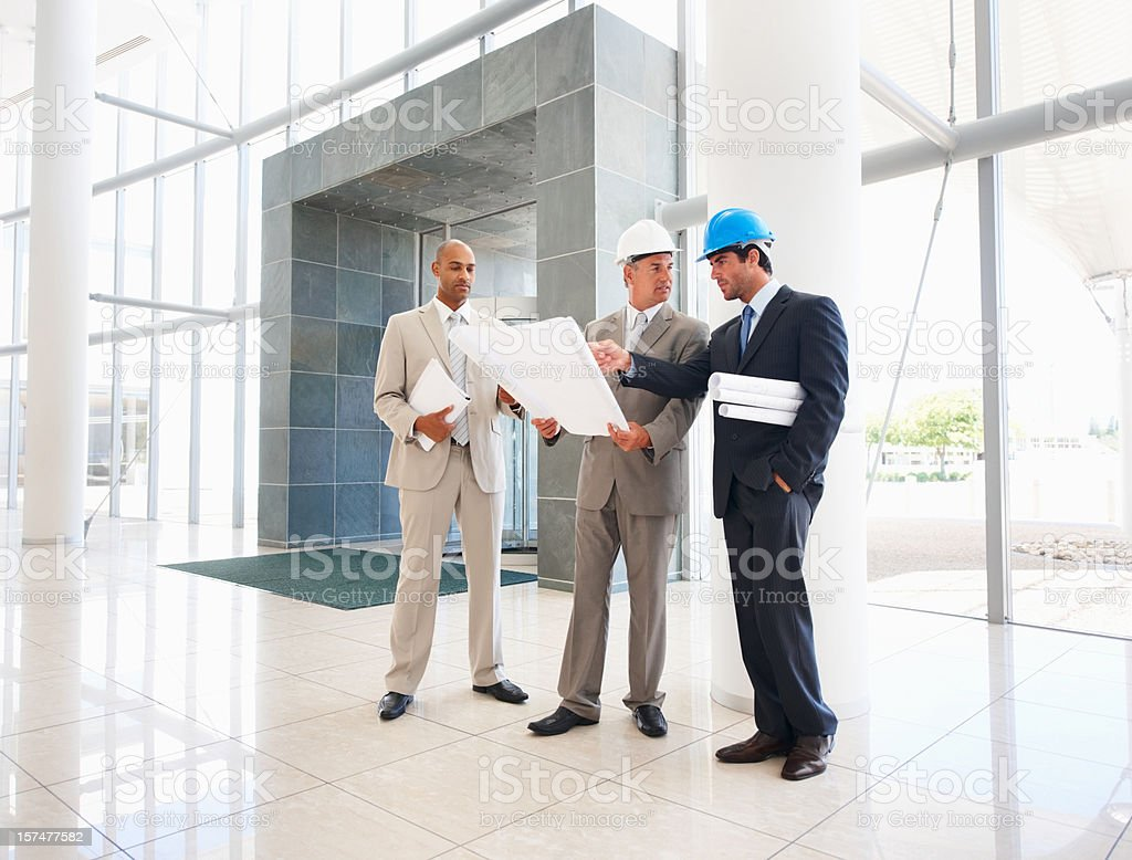 Business architects holding blueprints royalty-free stock photo