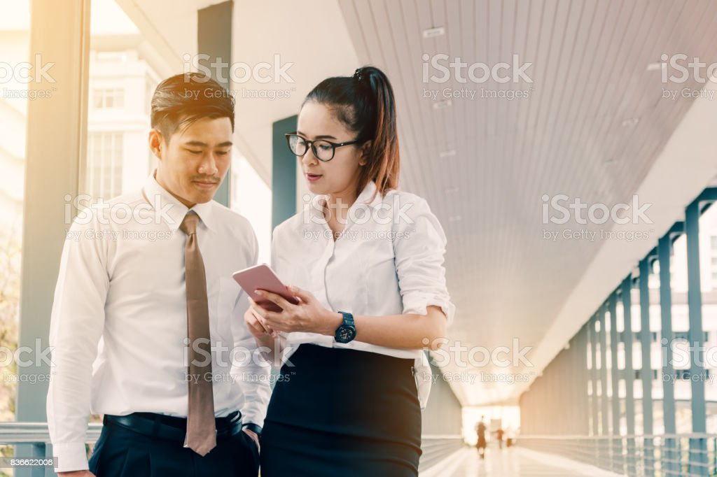 Business asian people talking about earnings results between the corridor of a company. stock photo