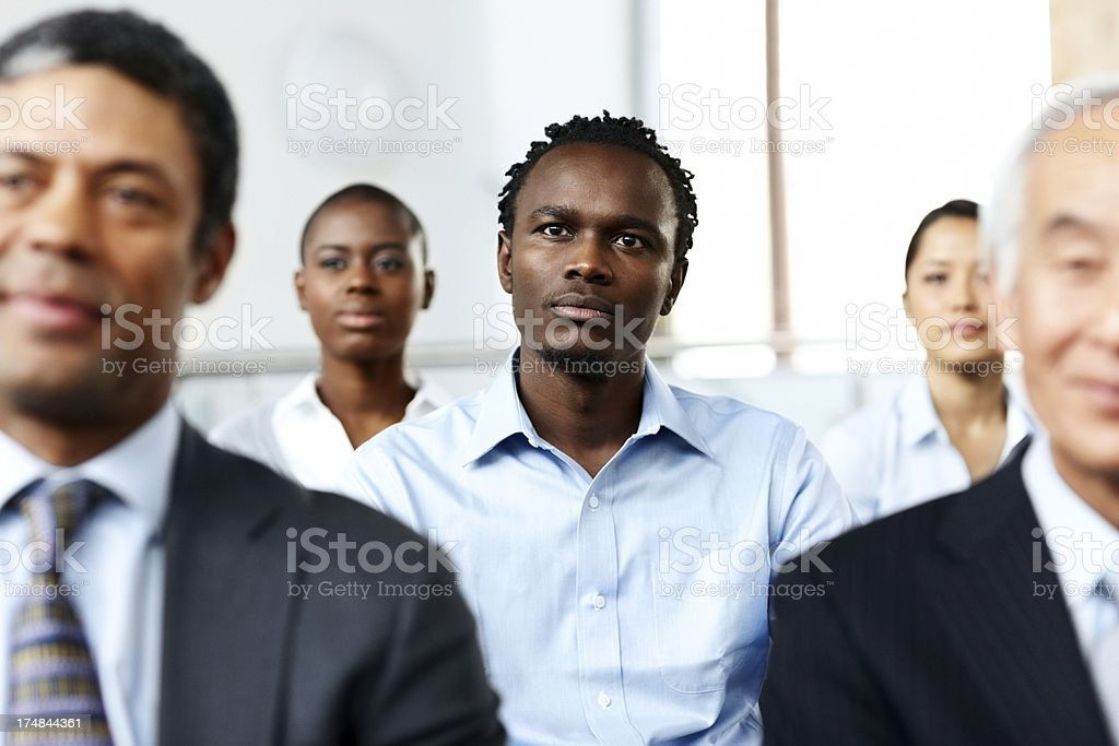 Business associates sitting attentively at seminar royalty-free stock photo