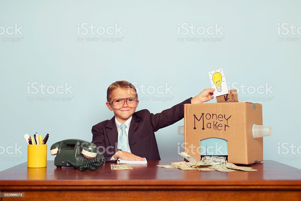 Business Boy Puts Ideas in Machine and Makes Money stock photo