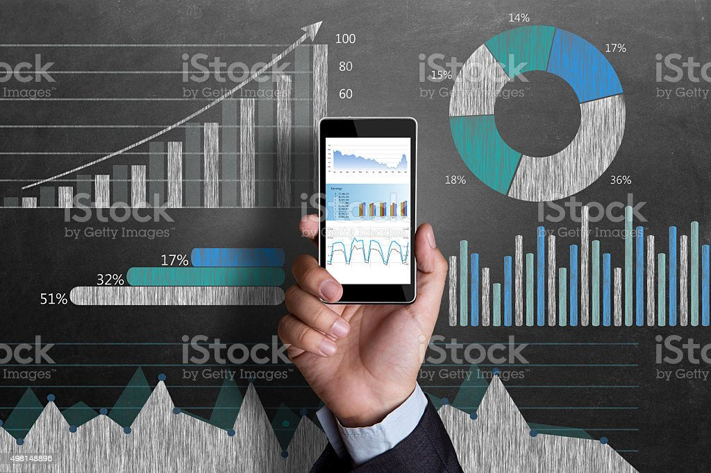 Business chart on blackboard with smart phone in human hand stock photo