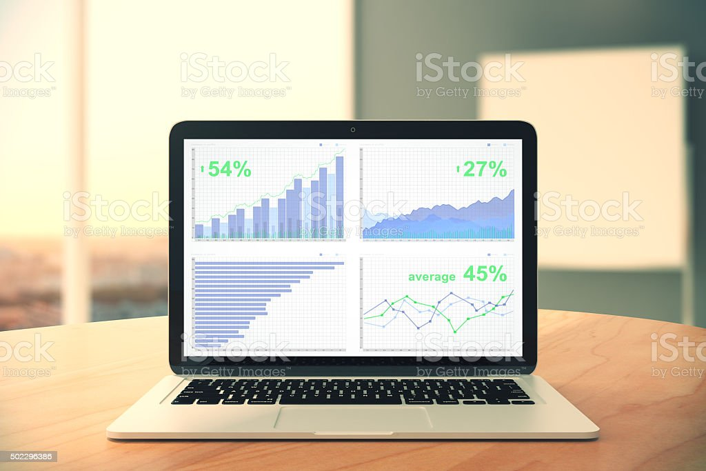 Business chart on laptop screen on wooden table stock photo