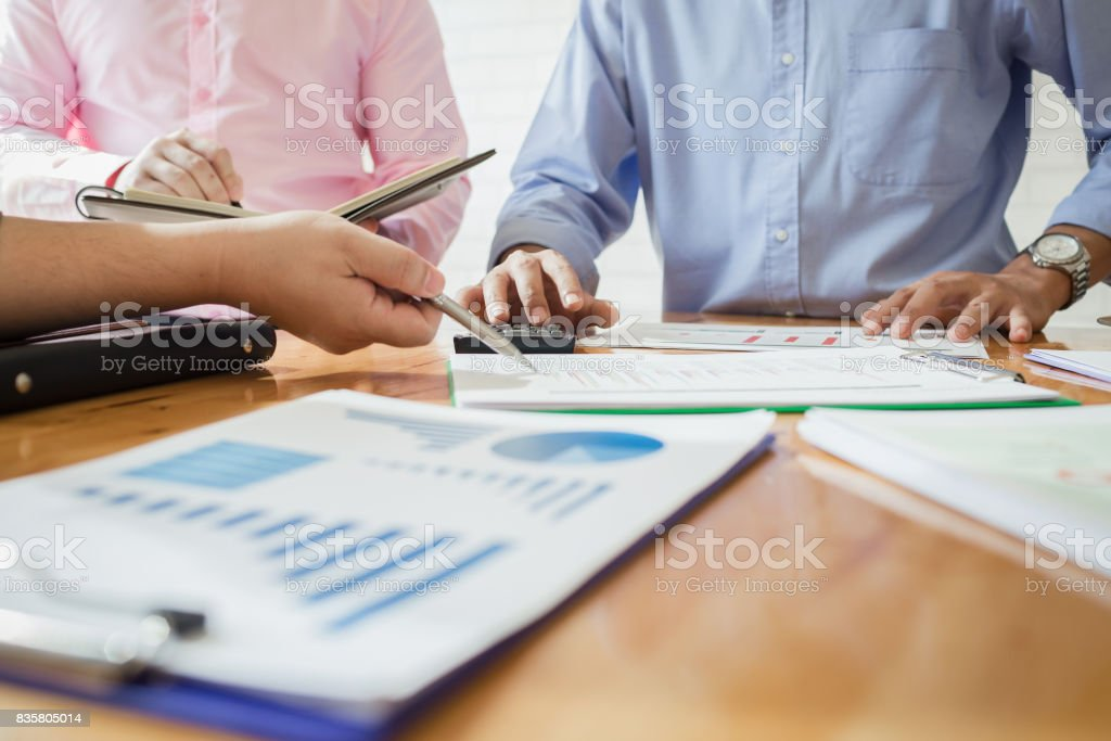 Business colleagues are meeting to determine their duties to summarize annual performance in the company's meeting room. The documents, business contracts placed on a wooden table. stock photo