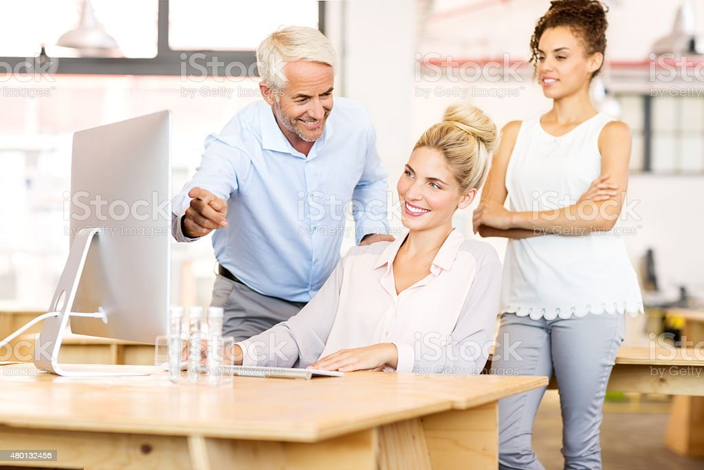 Business Colleagues Discussing Over Computer stock photo