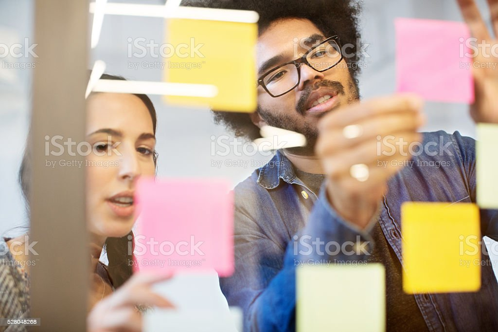 Business colleagues discussing over reminders stock photo