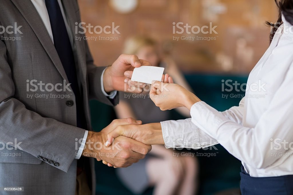 Business colleagues exchanging business card stock photo
