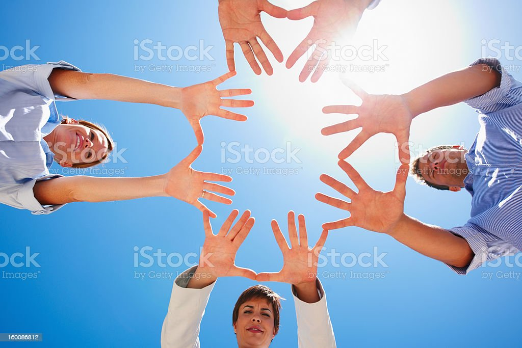Business colleagues gesturing against blue sky royalty-free stock photo