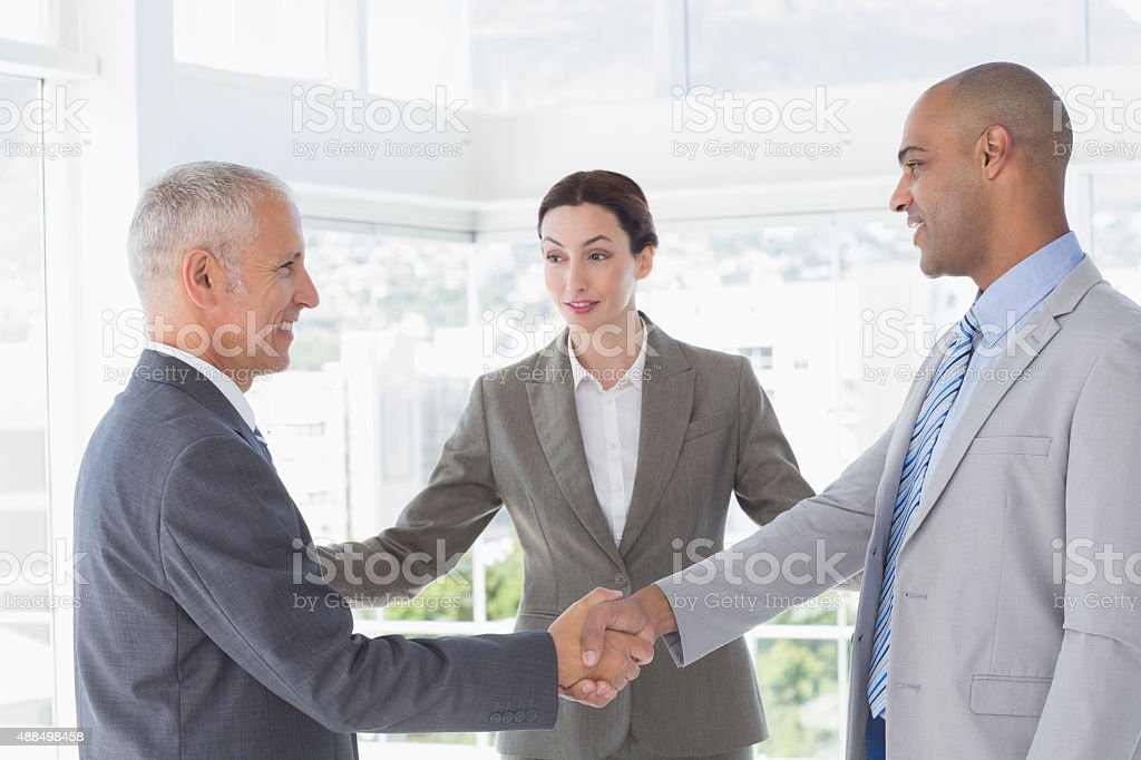 Business colleagues greeting each other stock photo