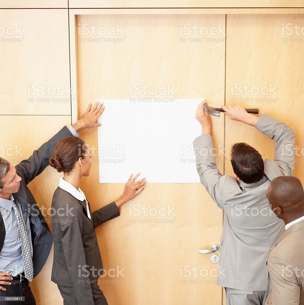 Business colleagues hammering billboard on wall royalty-free stock photo