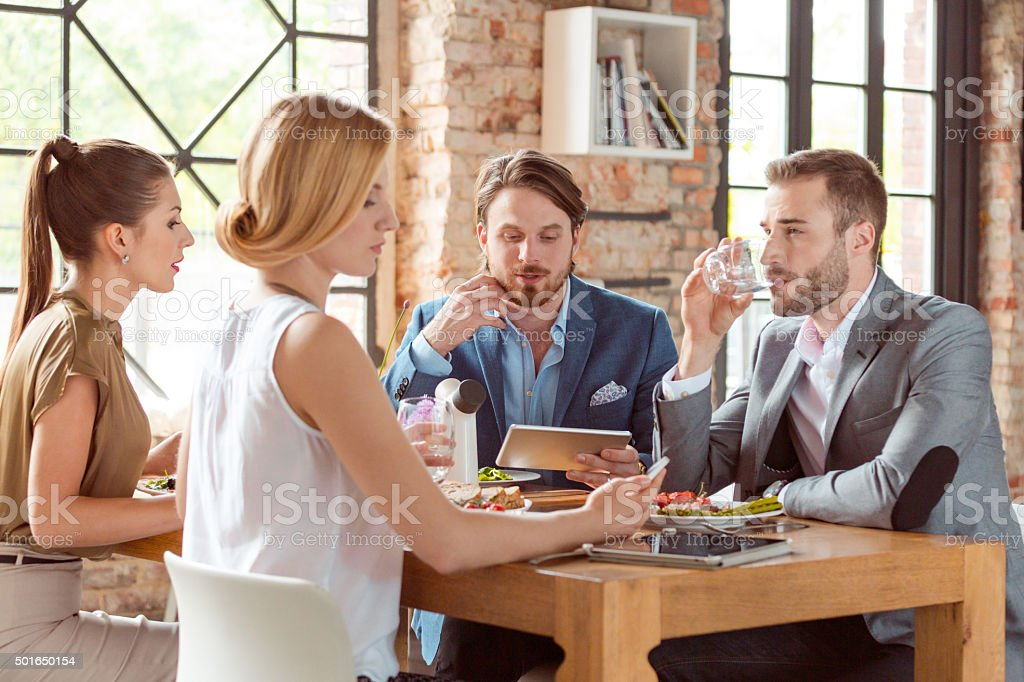 Business colleagues having lunch, bearded man using digital tablet stock photo