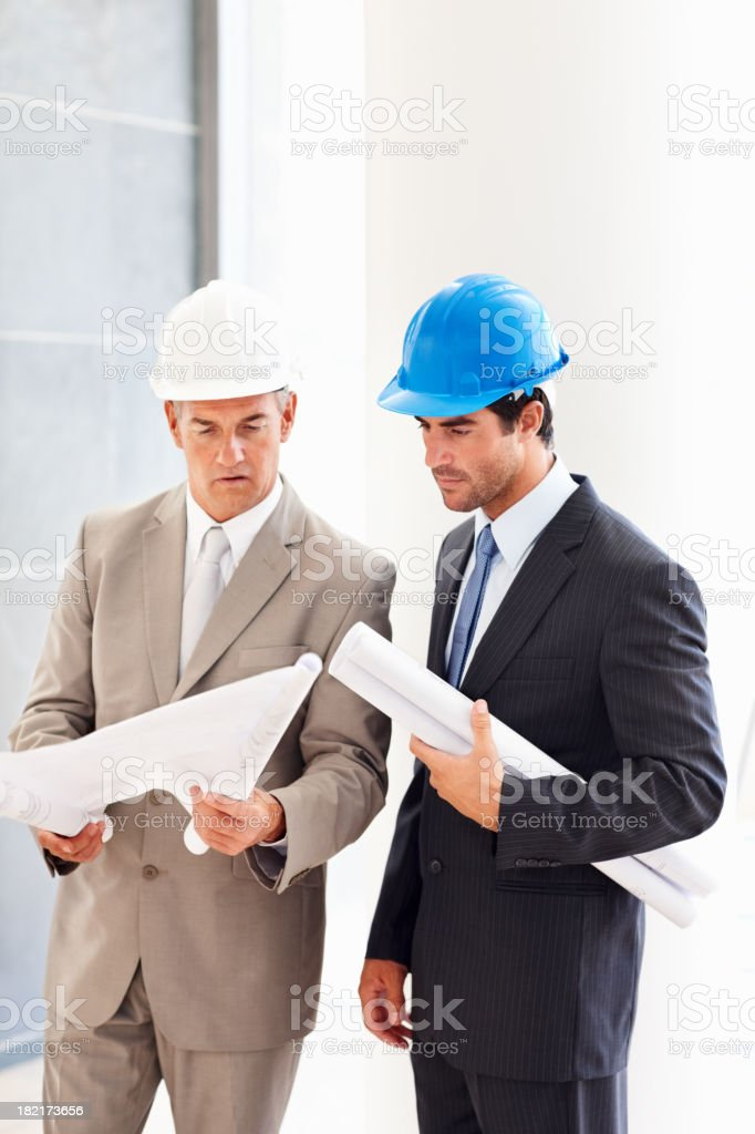 Business colleagues holding blueprints and discussing for project royalty-free stock photo