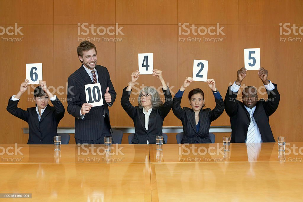 Business colleagues holding up cards with numbers, man standing stock photo