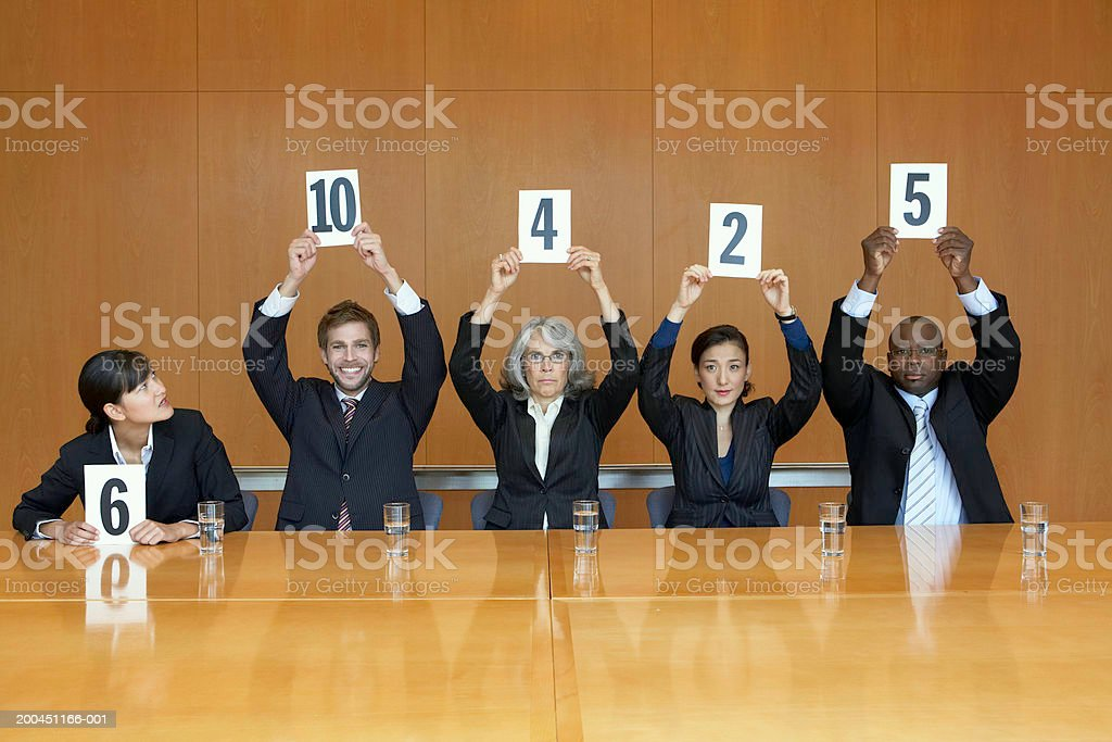 Business colleagues holding up cards with numbers stock photo