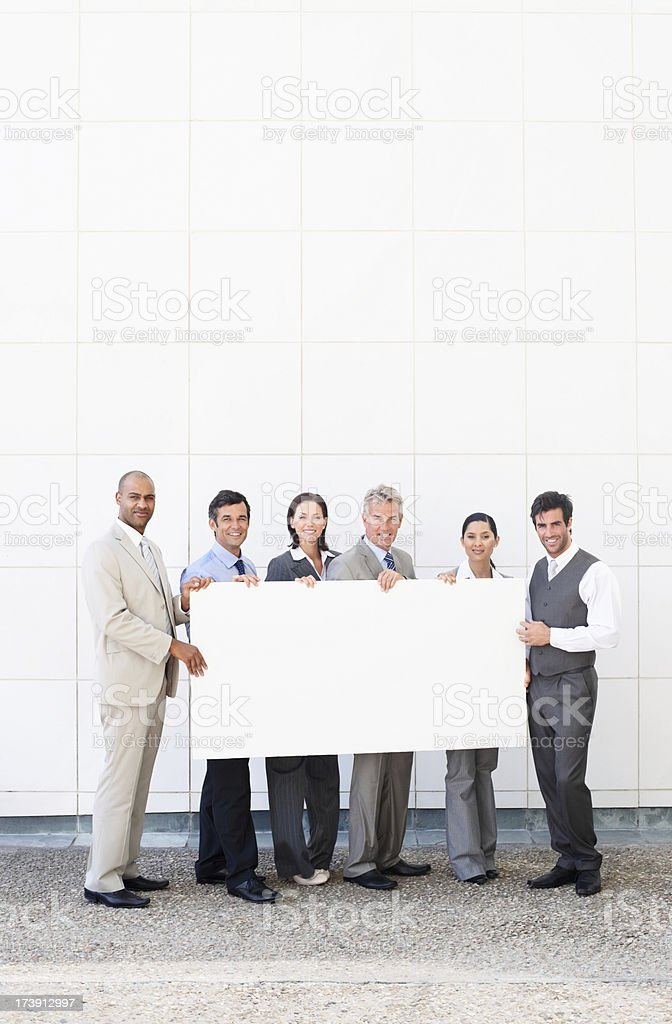 Business colleagues holding white billboard royalty-free stock photo