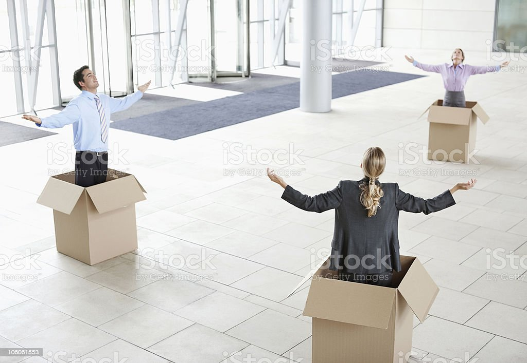Business colleagues inside cardboard boxes with arms outstretched at...