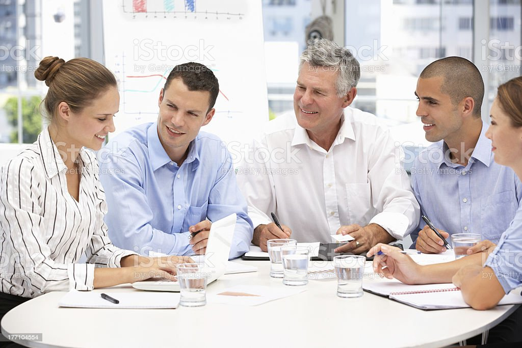 Business colleagues meeting with notepads, pens and a laptop royalty-free stock photo