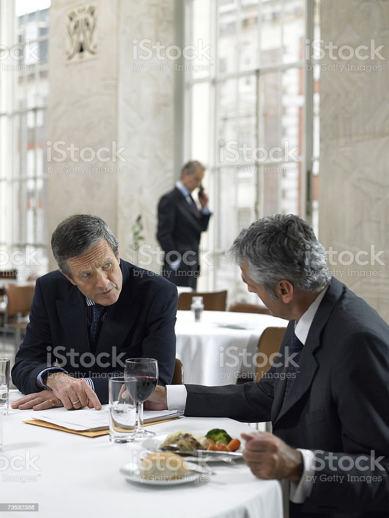 Business colleagues sitting at restaurant table, talking royalty-free stock photo