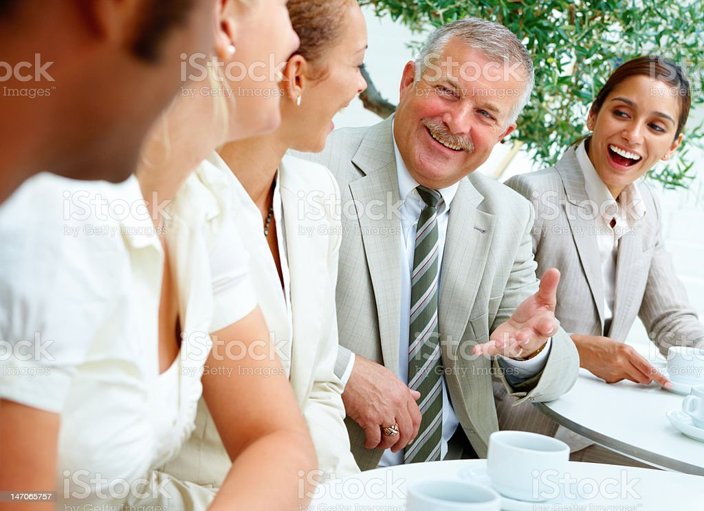 Business colleagues sitting together by table with coffee royalty-free stock photo