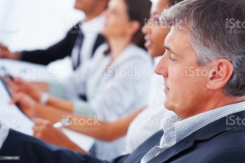 Business colleagues sitting together in a row stock photo