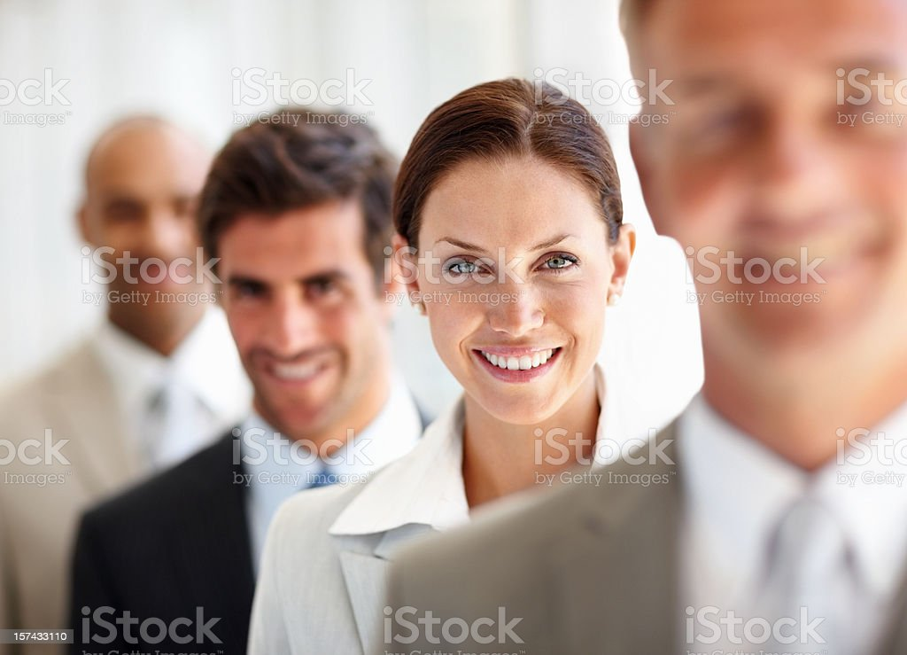 Business colleagues standing in a row whilst smiling royalty-free stock photo