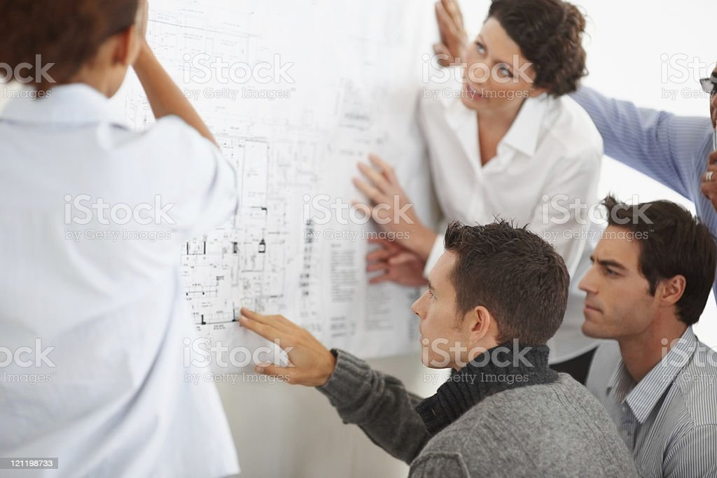 Business colleagues studying a chart displayed on the wall stock photo