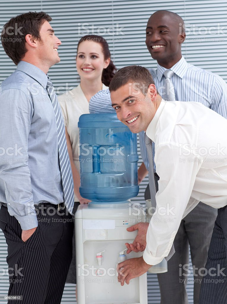Business colleagues talking around water cooler stock photo