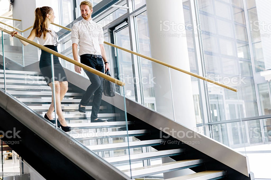 Business colleagues talking on stairs stock photo