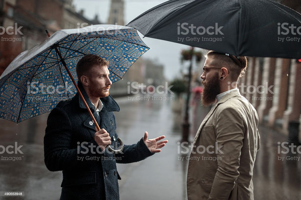 Business colleagues talking to each other on a rainy day. stock photo