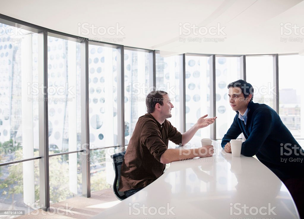 Business colleagues talking together in break room stock photo