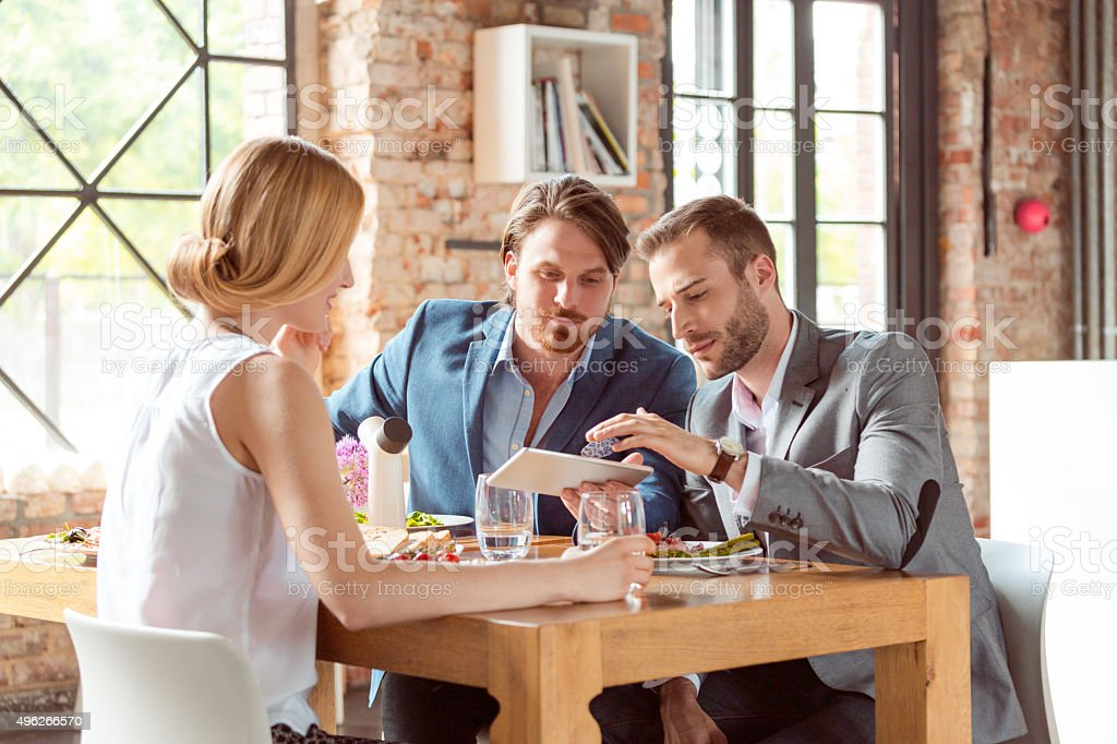 Business colleagues using a digital tablet during lunch stock photo
